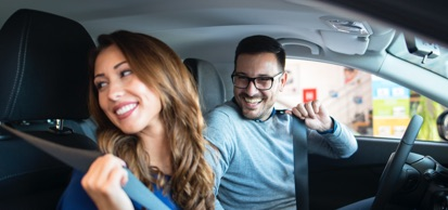 Woman And Man Smiling Putting On Seatbelts