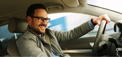 Smiling Man Driving Car Wearing Glasses
