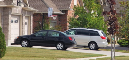 Vehicles Parked In Driveway Of Home In Residential Neighborhood