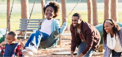 Young Family Playing On Swing Set In Playground