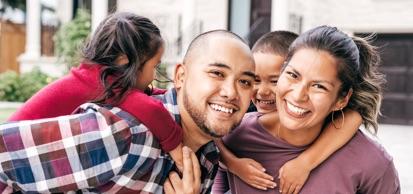 Young Family Smiling At Camera