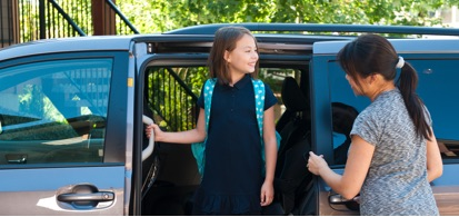 Young Girl Wearing Backpack Standing In Doorway Of Van With Mother Nearby